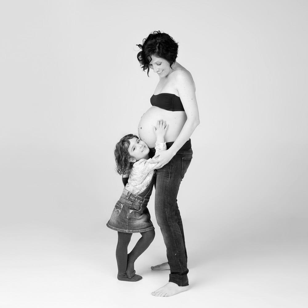 mare embarassada i filla agafant la panxa i mirant a camera
